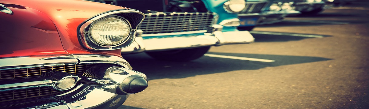 A zoomed in view of a row of vintage cars with only their front bumpers and wheels showing