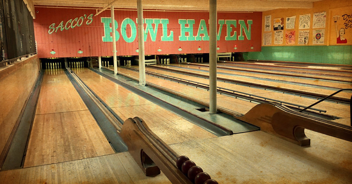 Several wooden lanes of a vintage bowling alley, facing toward the pins at Flatbread Company