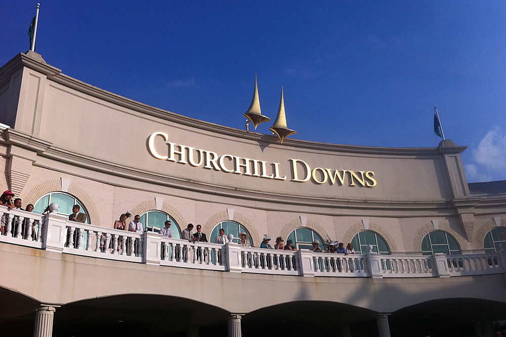 People looking over the second story deck at Chruchill Downs in Louisville.