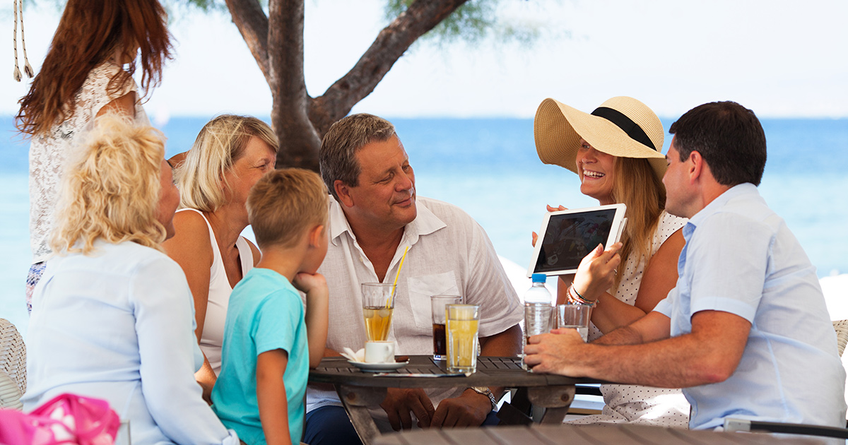 family sitting around a table on a beach vacation