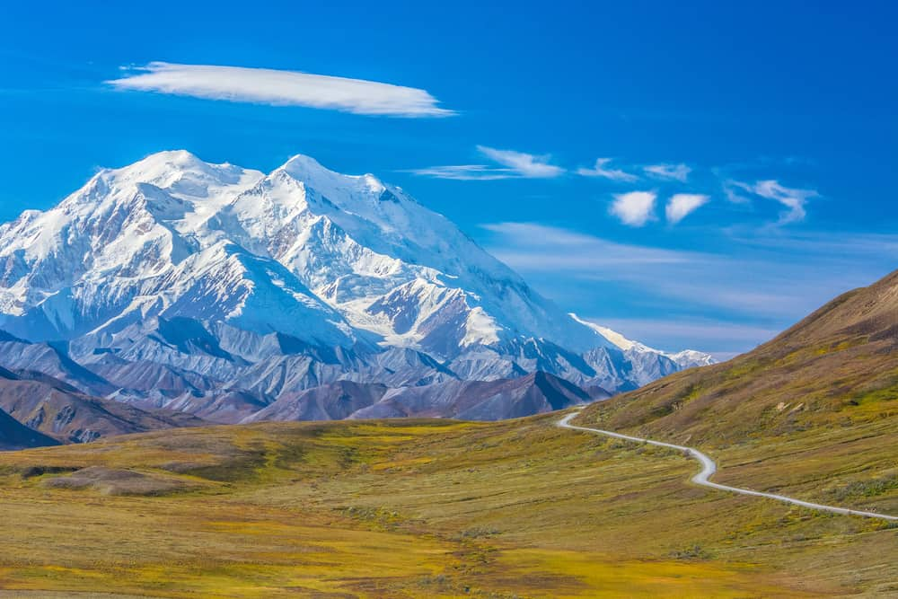 Rolling hills and a winding road set in round of snow-capped mountains in Denali National Park.