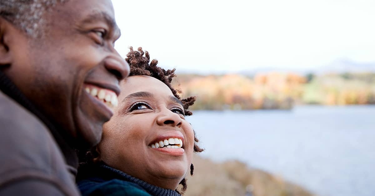A smiling senior couple overlook the water while on vacation.