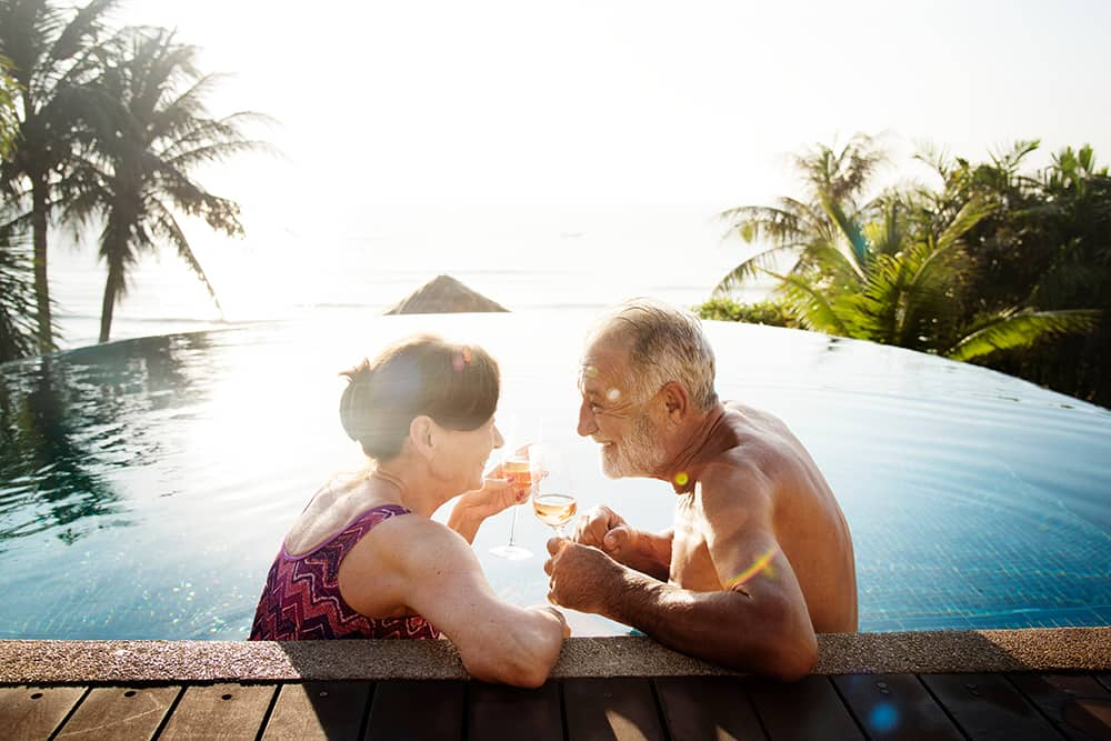 a senior couple having drinks in an infinity pool in a tropical place