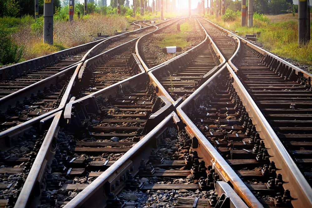 Train tracks leading into a sunset
