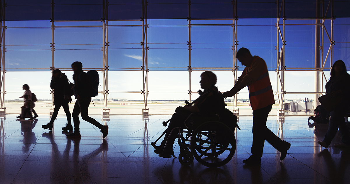 Silhouette of travelers going through the airport, specifically a younger man pushing an older woman in a wheelchair.