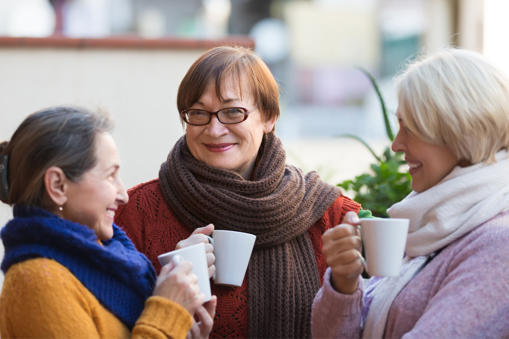 group of friends drinking cups of coffee outside
