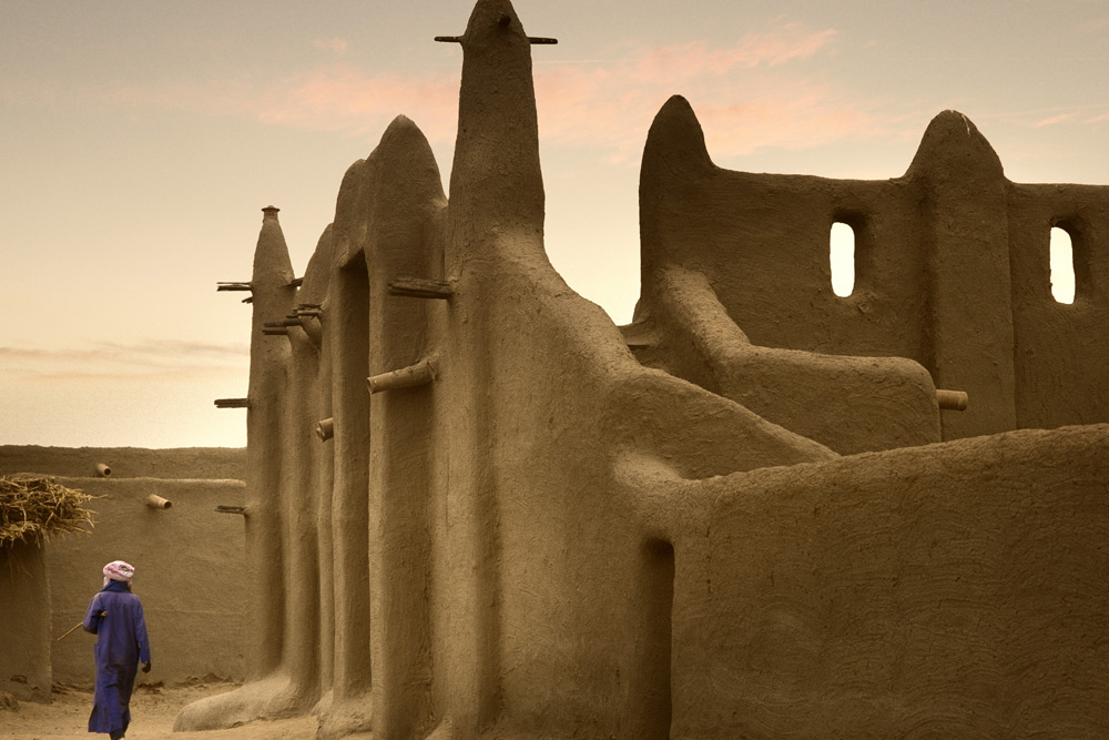 A man walking by a mosque built entirely of clay as the sun set on Mali, West Africa