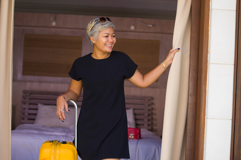 woman standing in hotel room with yellow suitcase