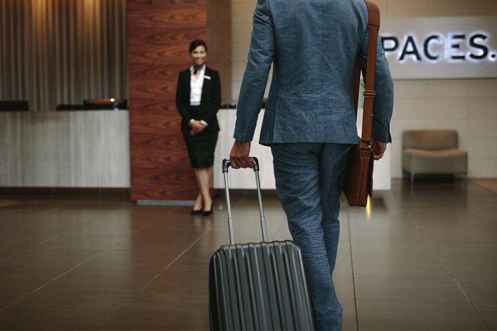 man walking toward airport gate with suitcase