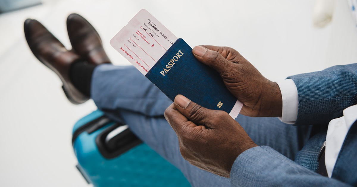 man's hands holding passport in airport