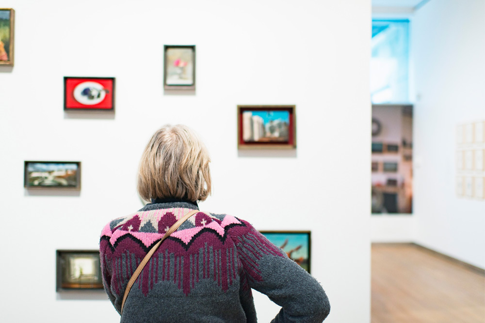 back of woman looking at art in a gallery