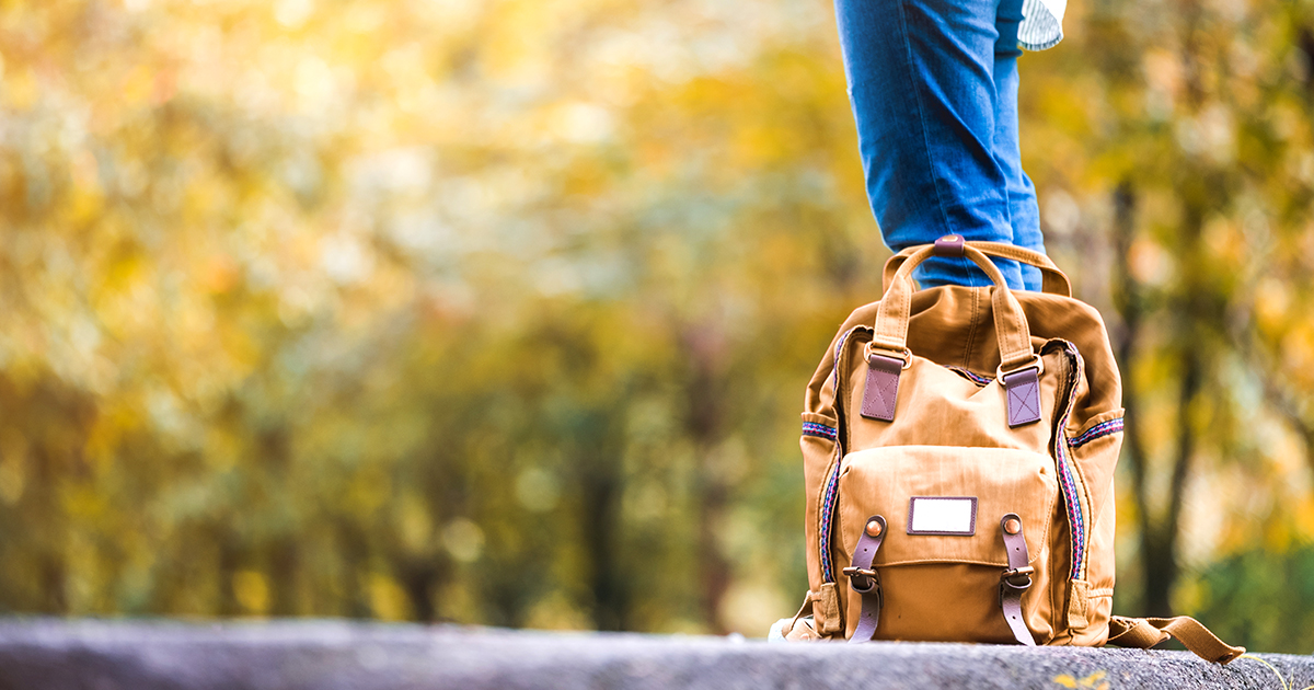 waist down view of woman with her backpack besides her on a countryside road