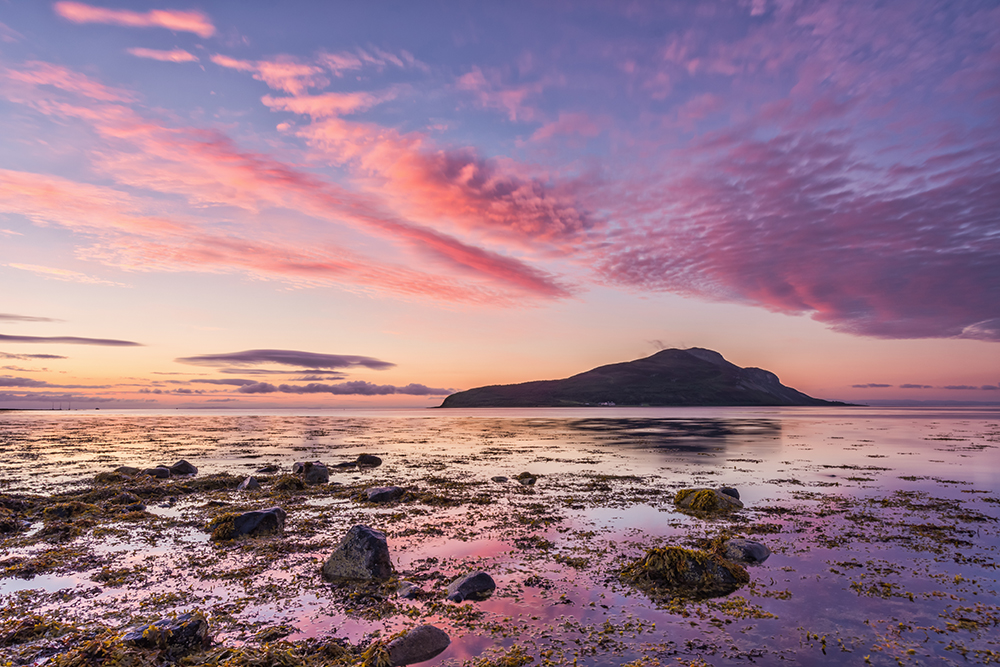 View of the Holy Isle at sunrise at low tide with purple and orange hued clouds
