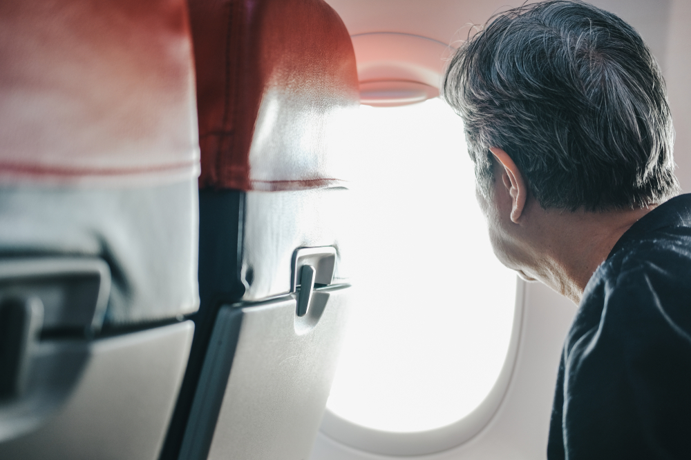 elderly senior woman looking through airplane window while traveling