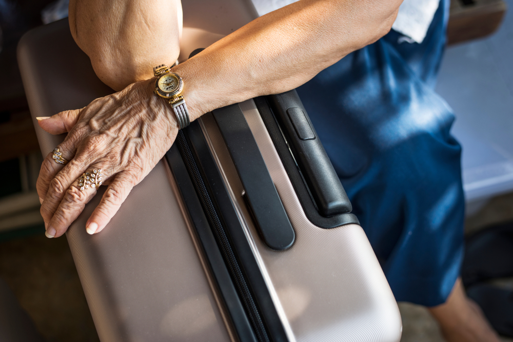 Senior woman waiting with her luggage traveling at a hotel