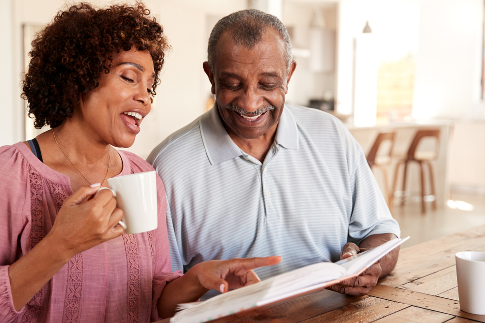 Senior man and daughter looking through photo album together