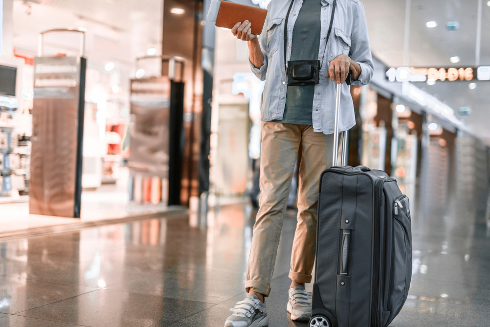 senior woman traveling in airport with suitcase and camera