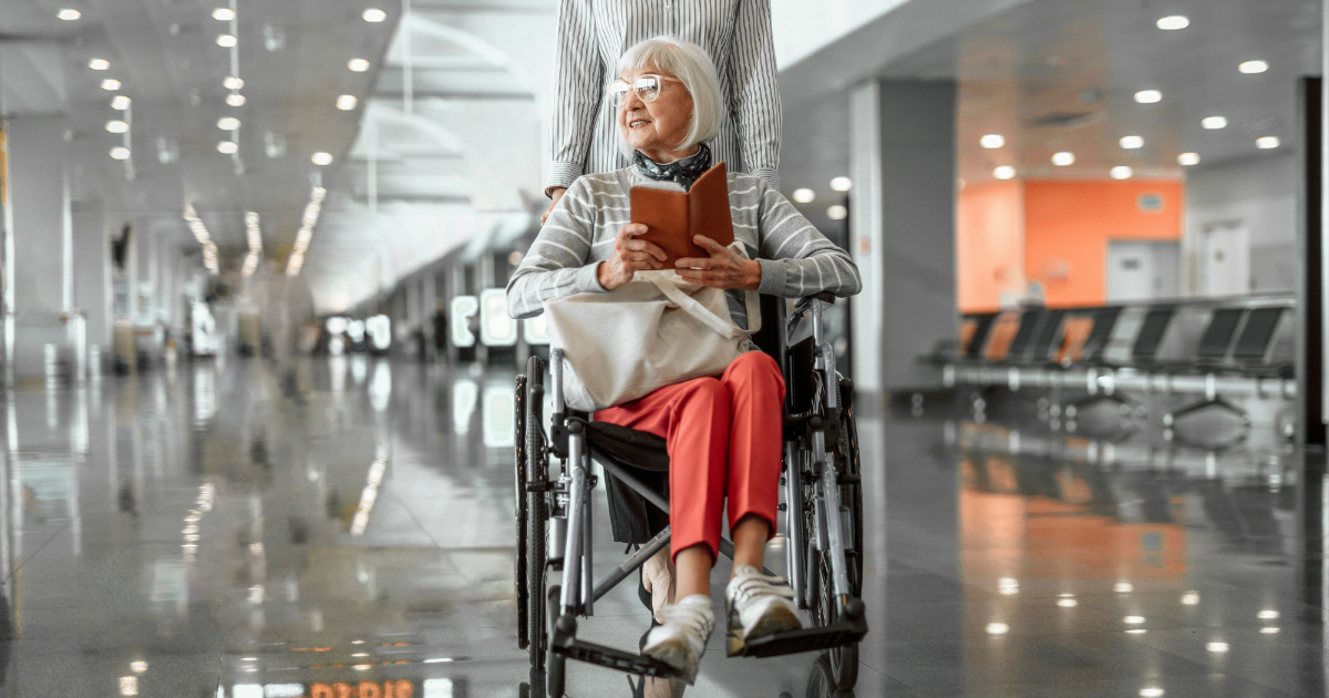 senior woman traveling in wheelchair in airport