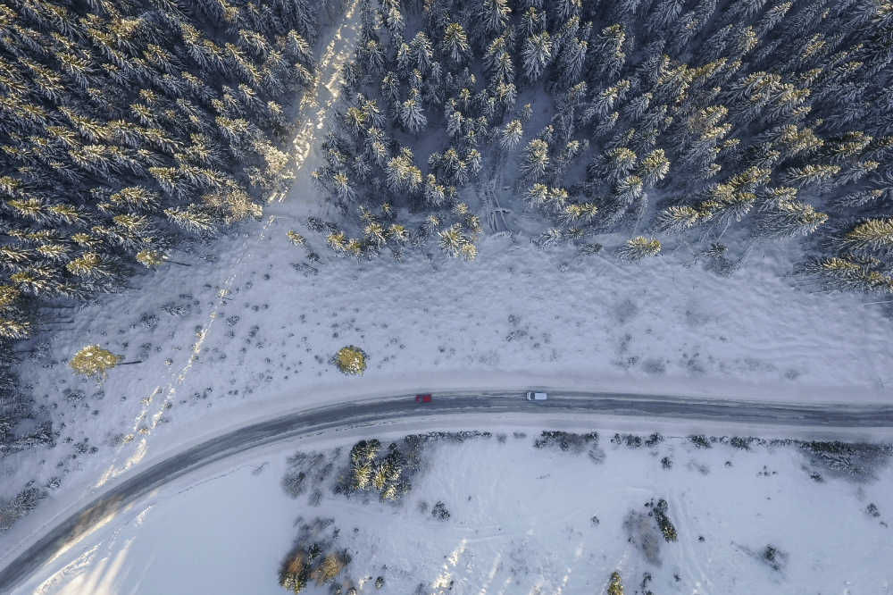 aerial view of two cars driving in the snow in the winter