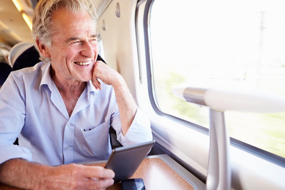 Senior Man Reading E Book while traveling On Train Journey