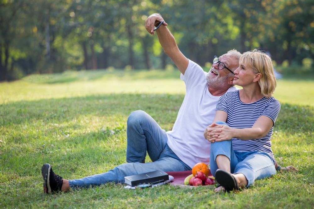 happy senior couple on vacation picnic taking photo together