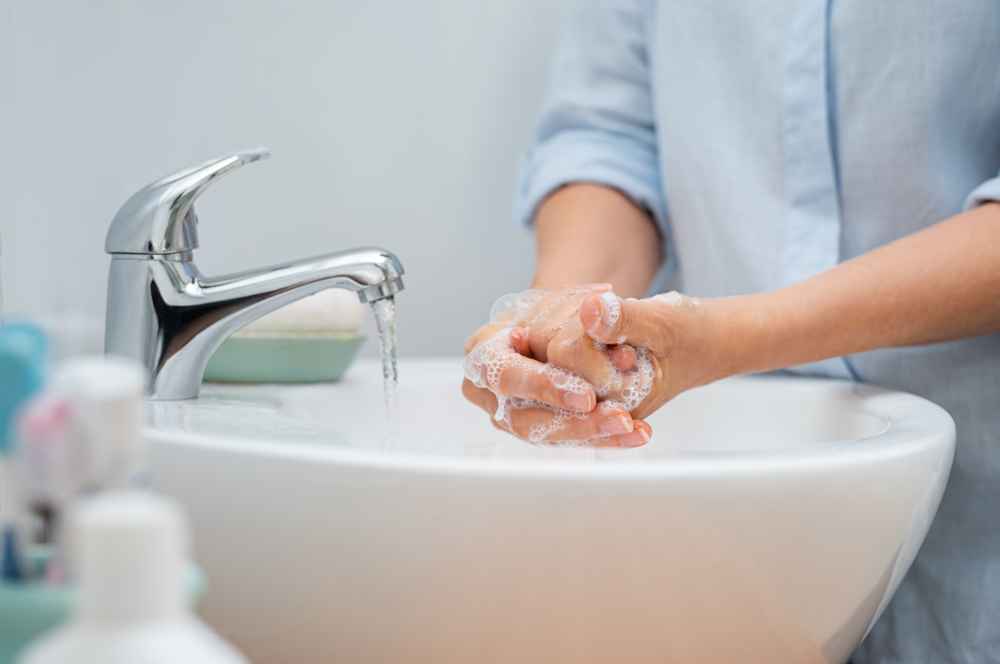 woman washing her hands to avoid getting sick
