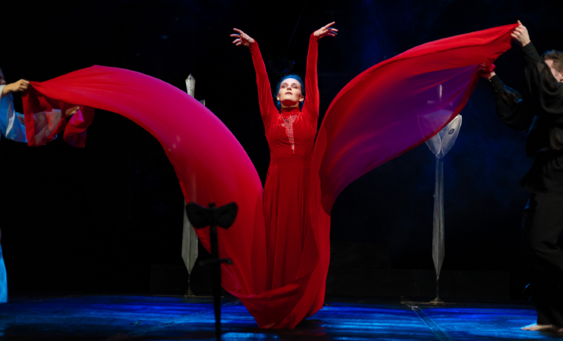 opera singer in red dress acting in dramatic live performance