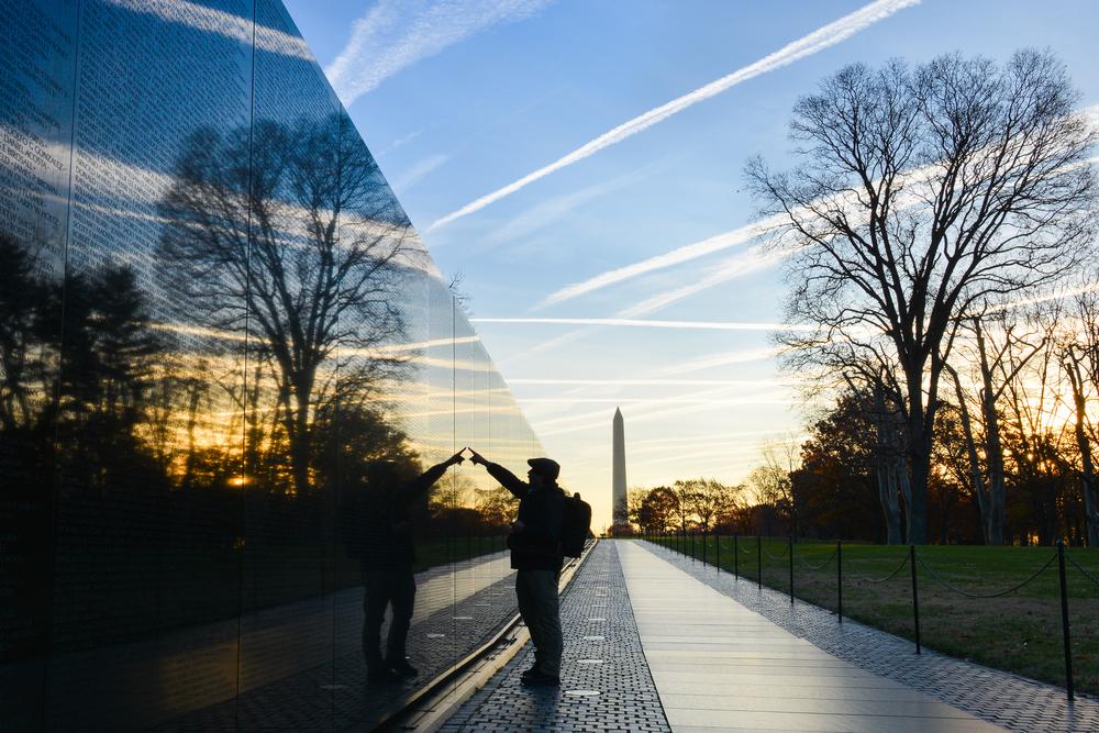 veteran looks for a name at Vietnam Veterans Memorial Wall at sunrise in Washington DC