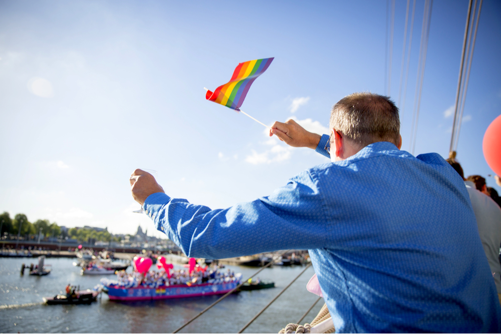 Man waving a rainbow flag during the annual event Gay Pride Parade, Euro Pride