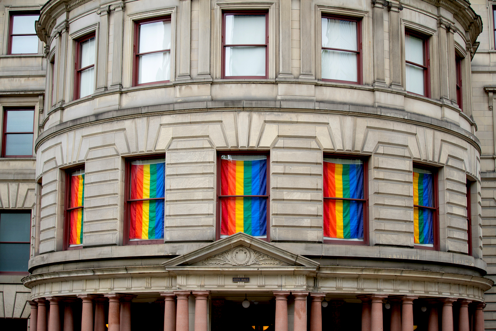 Portland city hall building with windows draped in LGBTQ rainbow flag