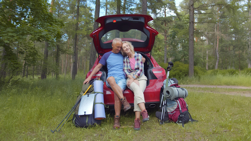 Portrait of mature man and woman hikers sitting in open car trunk