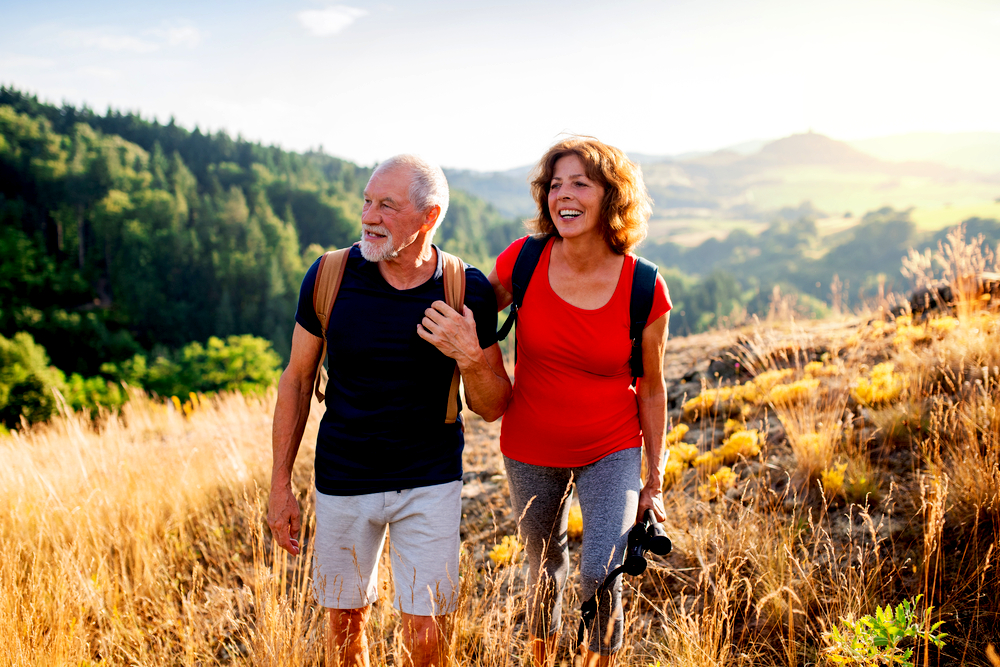 Senior tourist couple travellers hiking in nature, walking and talking