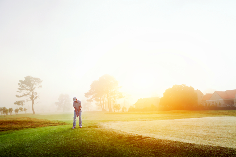 Golfer chipping onto the green at sunrise on the golf course in misty condition