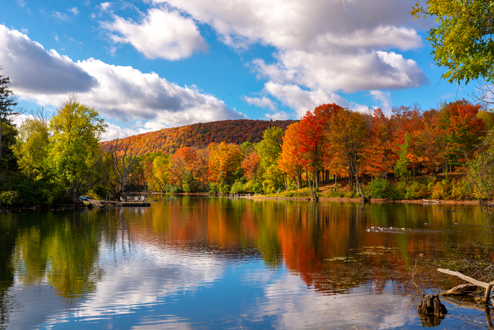 Adirondacks in upstate NY. Mirror Lake in Lake Placid, New York, on a sunny autumn day with colorful fall foliage on the mountains in the background