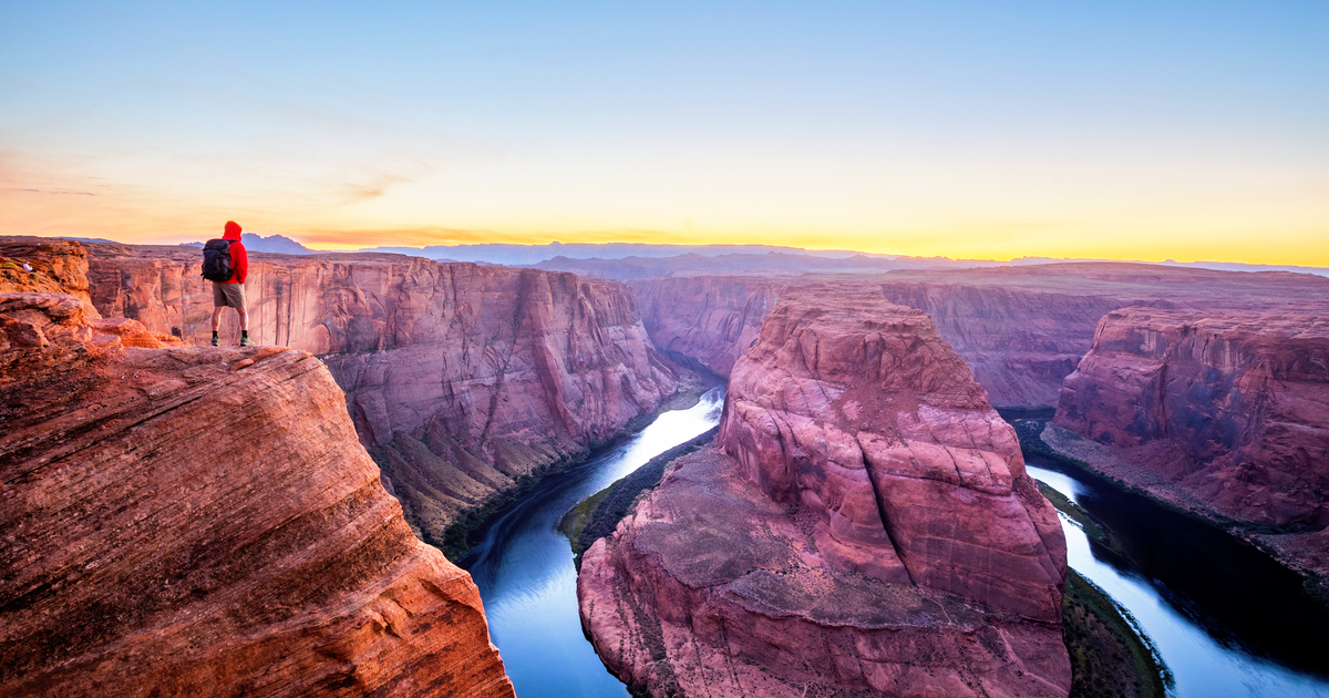 A male hiker is standing on top of steep cliffs enjoying the beautiful view of Colorado river flowing at famous Horseshoe Bend in beautiful post sunset twilight on a summer evening, Arizona, USA